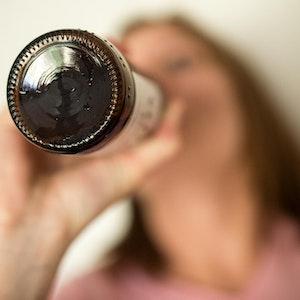 Eine Frau trinkt aus einer Flasche.