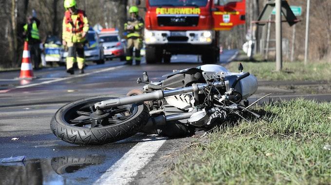 Ein stark beschädigtes Motorrad liegt auf einer Landstraße.