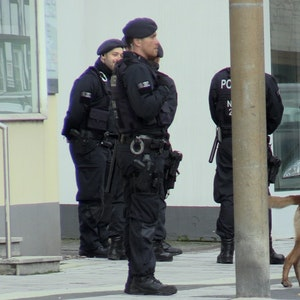 Zum Teil vermummte Einsatzkräfte stehen vor einem Haus.
