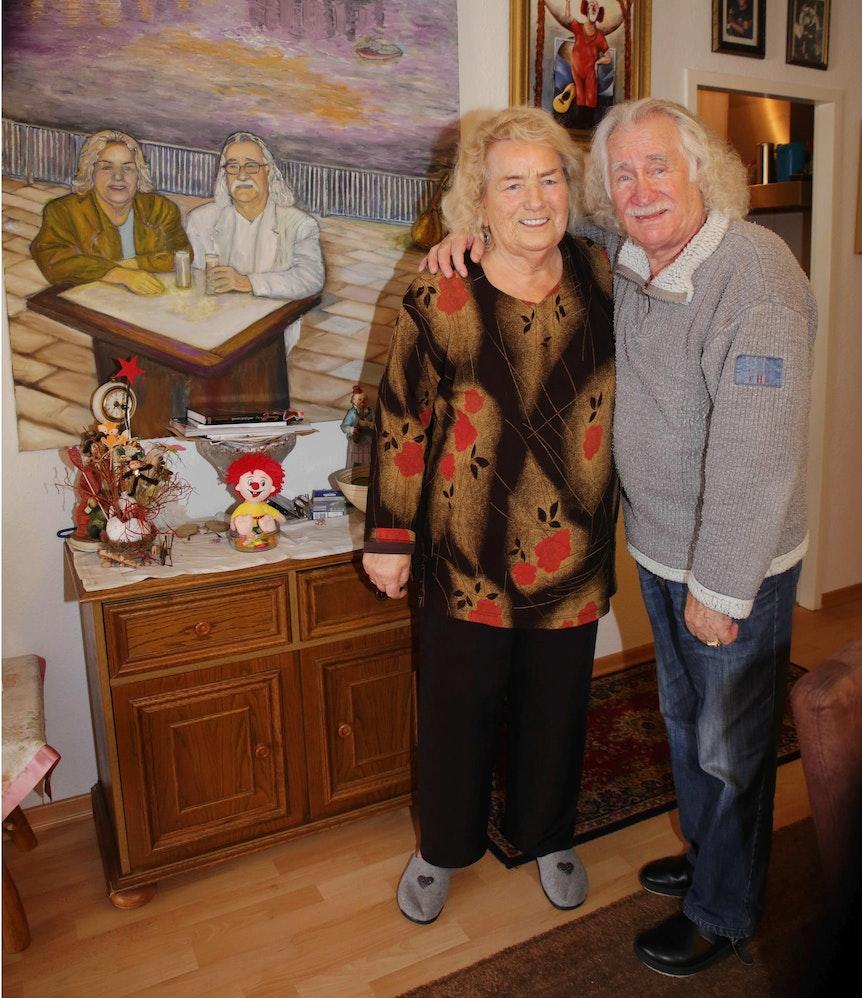 Hans Süper und Helga Süper stehen Arm in Arm im Wohnzimmer.