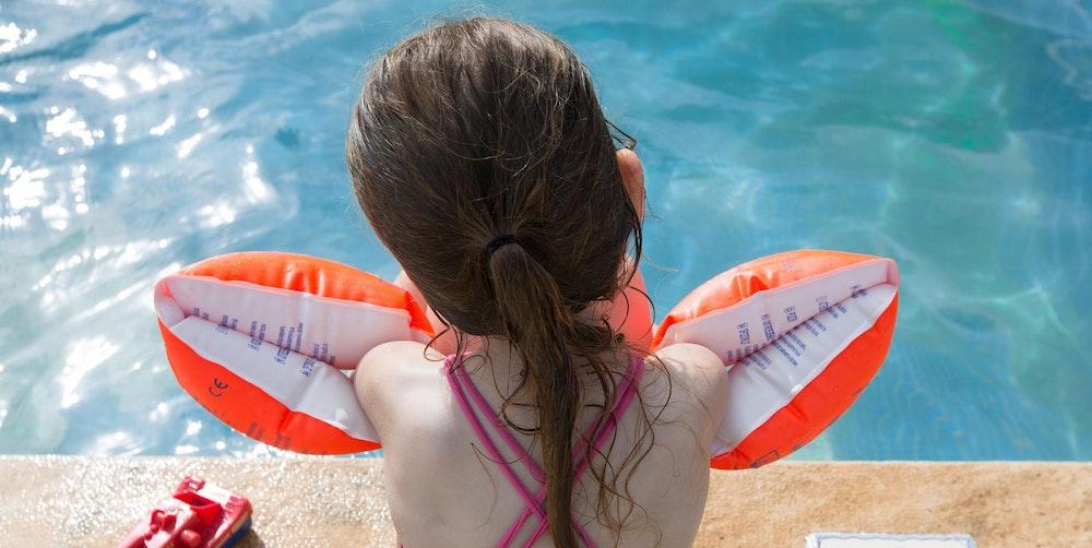 Ein Mädchen sitzt mit Schwimmflügeln am Beckenrand.
