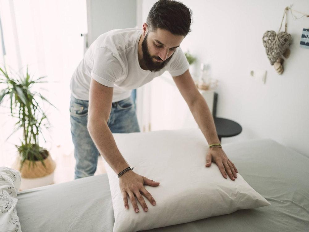Mann macht sein Bett imago