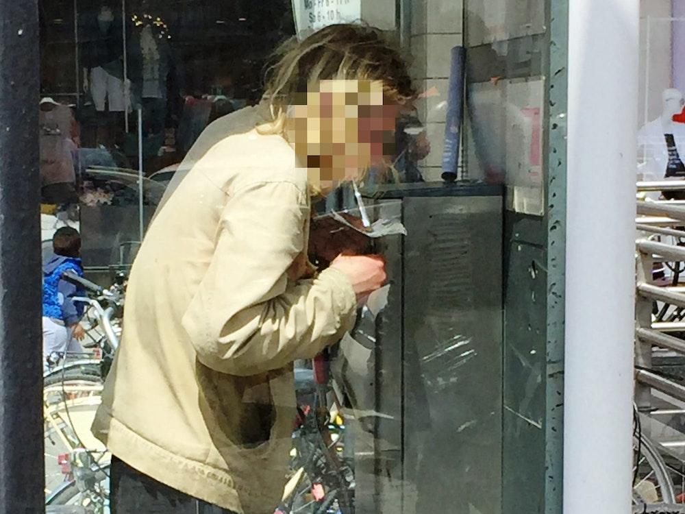 Ein Mann konsumiert Heroin in einer Telefonzelle.