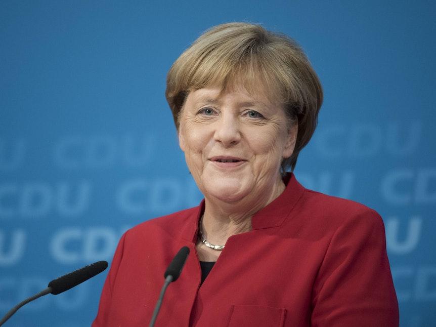 Angela Merkel grinst bei einem Pressestatement am Rednerpult.
