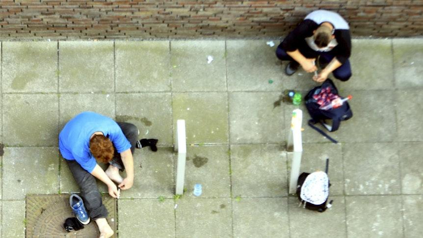 Zwei Männer sitzen auf dem Boden und konsumieren Heroin.