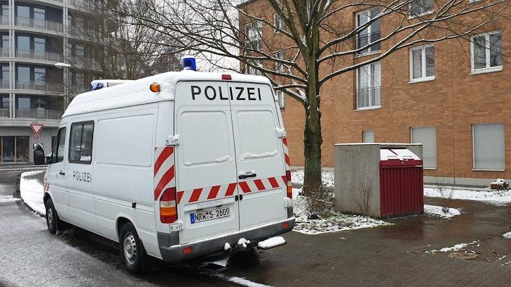 Ein Kastenwagen der Polizei steht vor einem Mehrfamilienhaus
