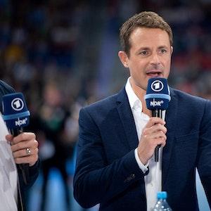 Alexander Bommes moderiert bei einer EM-Übertragung mit einem Mikrofon in der Hand..