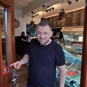 Christos Charalabidis zeigt den Jode-Lade-Sticker an seinem Laden Tischlein deck dich.