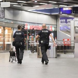 Polizisten laufen mit einem Diensthund durch den Hauptbahnhof Gelsenkirchen.