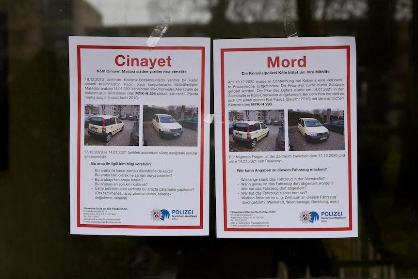 Zwei Zettel der Polizei mit Autofotos und der Bitte um Hinweise kleben an einer Glasscheibe.