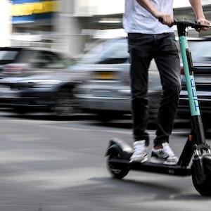 Kölner fährt mit E-Roller durch die Stadt Köln.