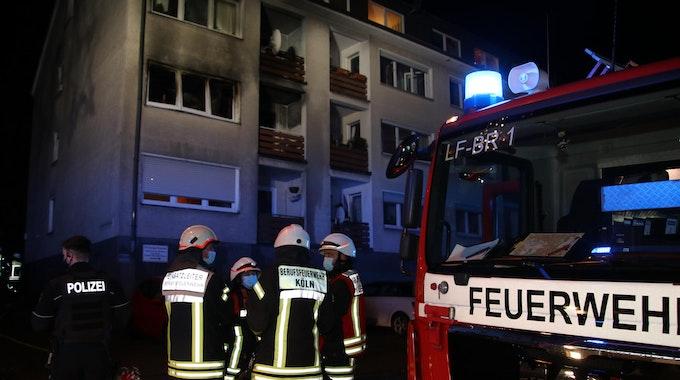 Feuerwehrmänner stehen neben einem Einsatzfahrzeug.