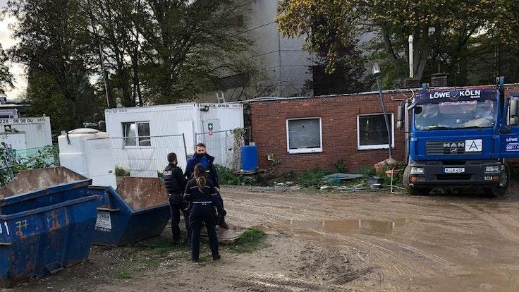 Yüksel Aker steht mit zwei Polizisten auf seinem Firmengelände in Köln.