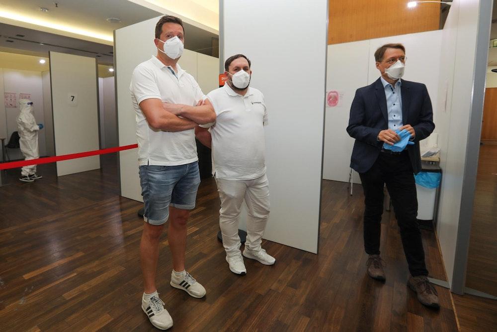 Karl Lauterbach steht im Testzentrum und unterhält sich mit den Betreibern