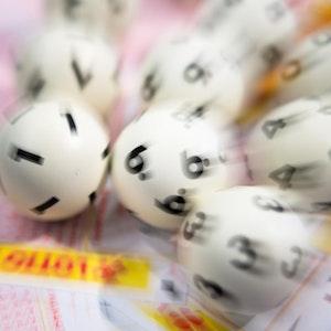 Das Foto zeigt Lotto-Kugeln und einen Tippschein.