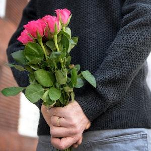 Mann überrascht Frau mit Blumenstrauß