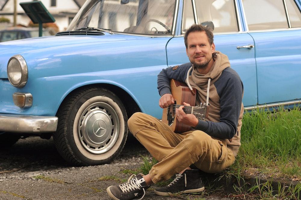 Mike Kremer von Miljö spielt sitzend Gitarre vor einem Auto