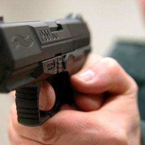 Ein Mann hält eine Pistole in die Kamera.