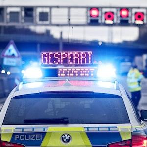 """Ein Polizeiwagen steht auf der Autobahn, auf seinem Dach befindet sich ein Hinweisschild mit dem Wort """"Gesperrt""""."""